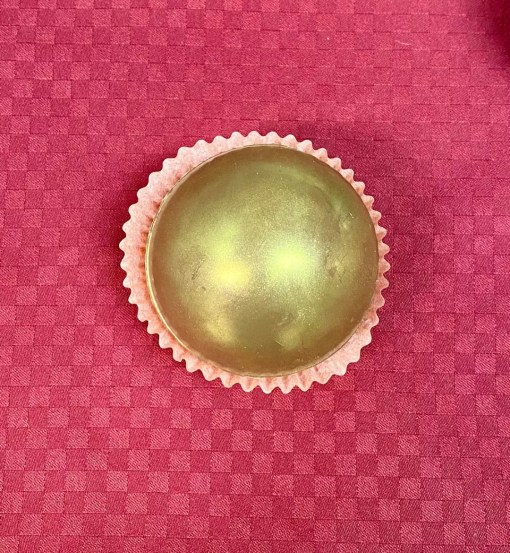 A dark chocolate magic drinking chocolate orb that is decorated in gold luster dust, in a cup on a red background.