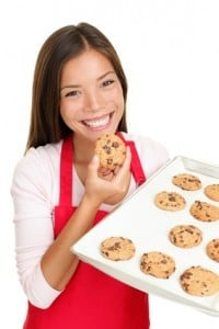 baking woman eating Chocolate Chip Cookie happy