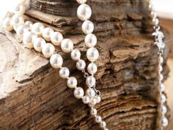 A pearl necklace on a wooden stand.