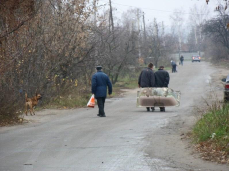 Dowód rzeczowy numer 1 - zdjęcie trzech mężczyzn ciągnących wannę, a po lewej stronie trzynogi pies.