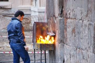 Kościół w centrum Erywania. Młody mężczyzna odmawia modlitwę i zapala symboliczną świeczkę.