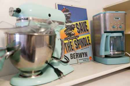Among my teal KitchenAid mixer and teal coffee maker - my Save The Spindle poster.