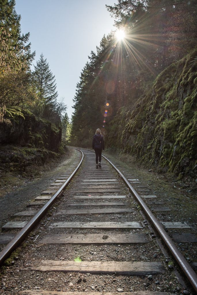 Blonde girl walking along a set of train tracks at Goldstream Provincial Park as a sunbeam peaks through the trees.