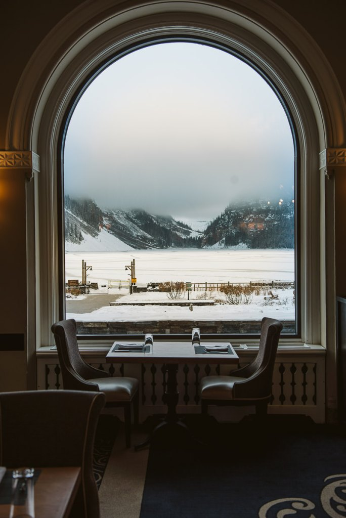 A view from one of the Fairmont Chateau Lake Louise windows overlooking the frozen Lake Louise on a cloudy day.