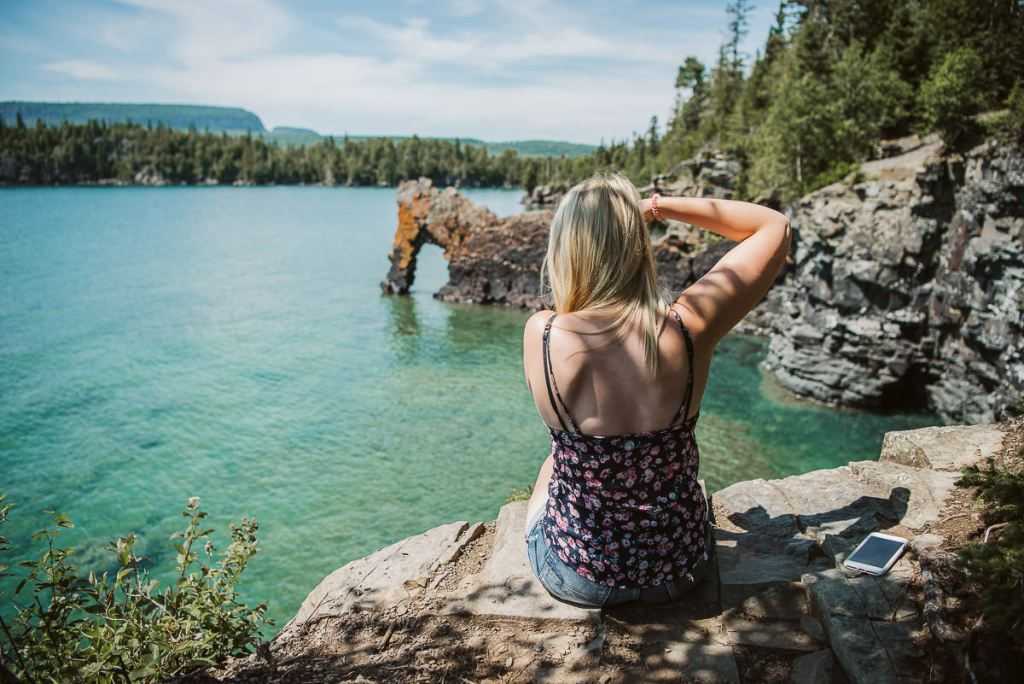 Blonde girl taking a photo of the sea lion in sleeping giant provincial park in Northern Ontario.
