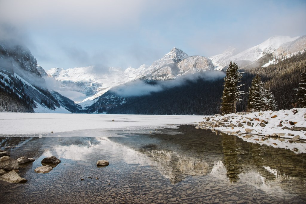 A half frozen Lake Louise in November. With a slight covering of low clouds with the mountains reflecting in the open water.