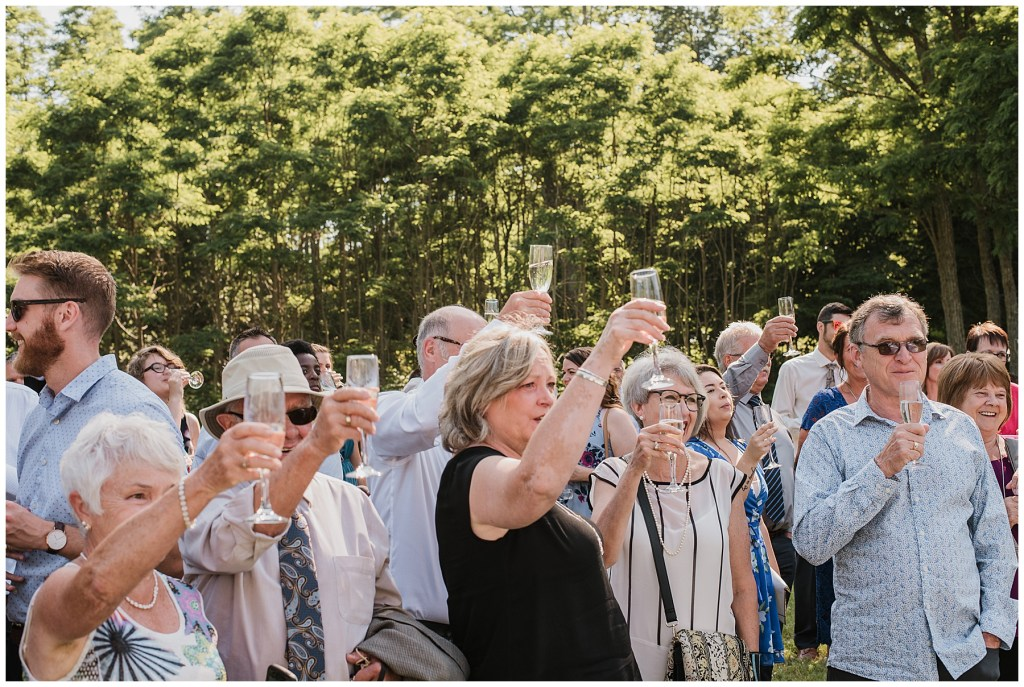 Guest toast to bride and groom on grounds of crystal cliffs wedding venue