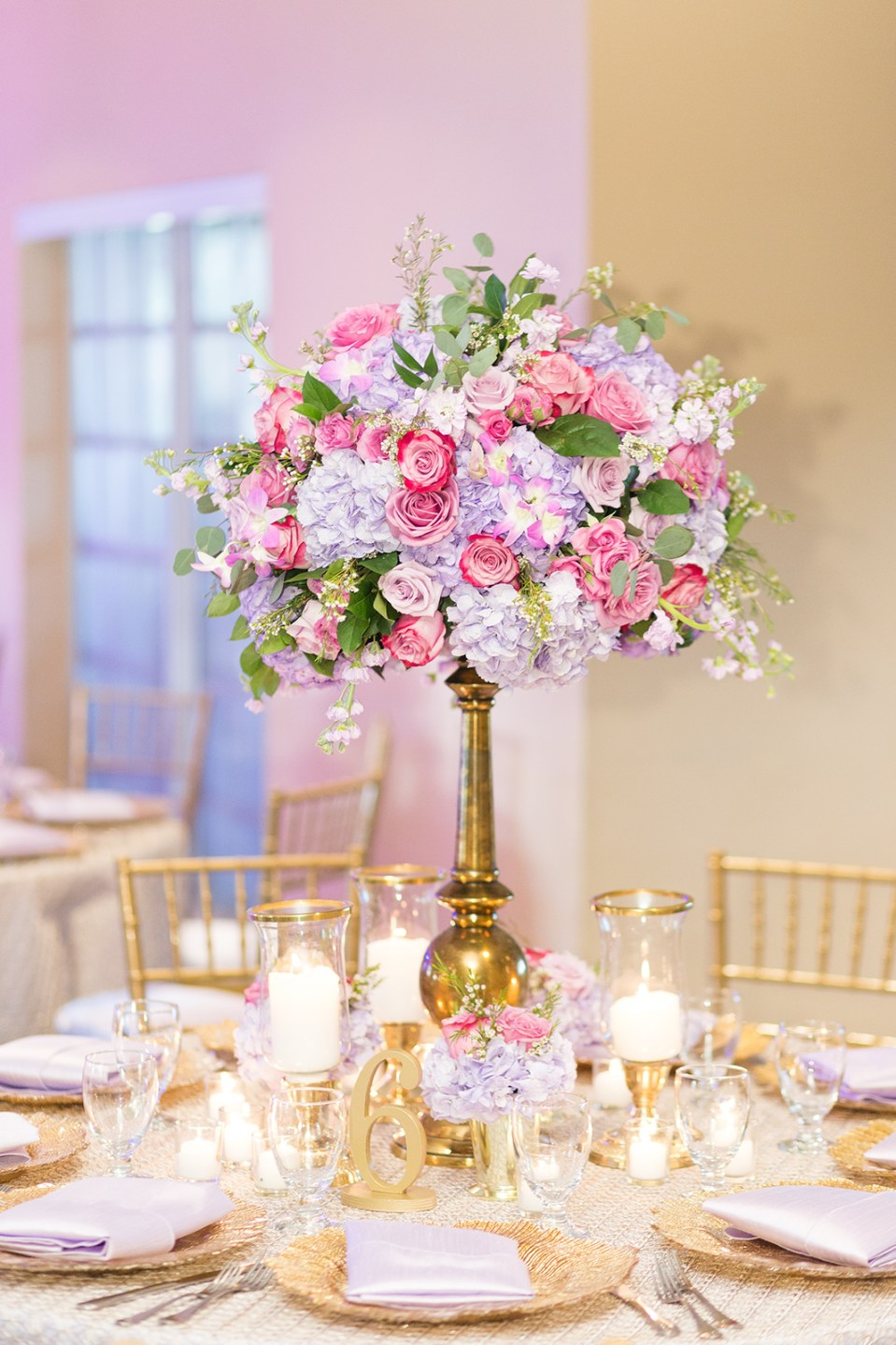 pink and purple flowers in large gold vase at wedding reception
