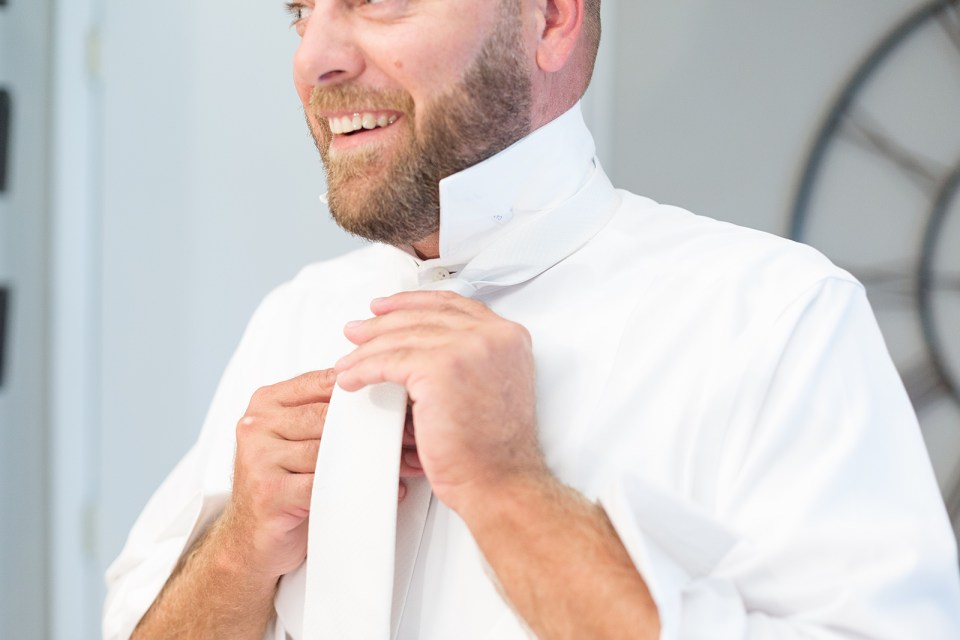 groom putting on white tie