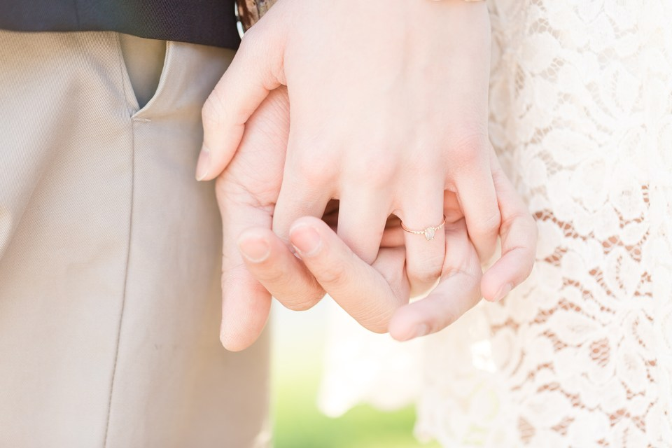 closeup of man and woman's hands holding each other with engagement ring visible