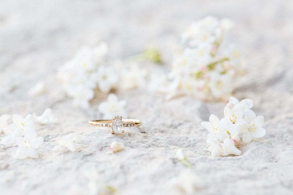 closeup of teardrop engagement ring on grey stone with white flowers in the background