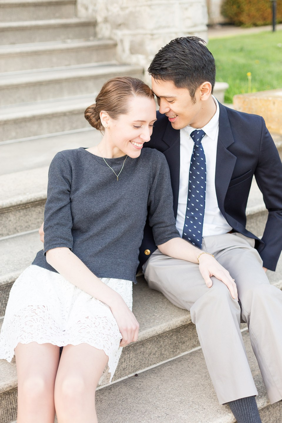 seated couple smiling while taking their Fergus Ontario engagement photos at the Wellington County Museum