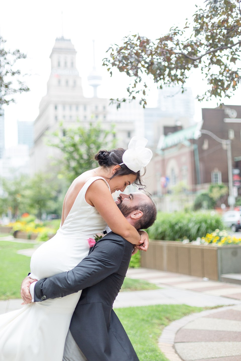 groom picking up his bride for a kiss in a small park in front of the CN Tower toronto