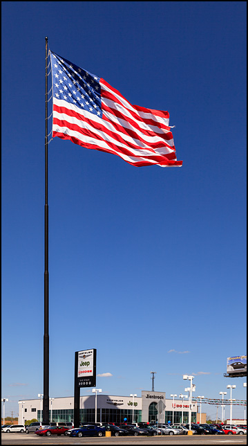 A giant, 50 X 80 foot flag flies from a 232 foot flagpole at Glenbrook Dodge Chrysler Jeep in Fort Wayne, Indiana. Is it the largest regularly flown in the U.S.? Photo by Christopher Crawford, who sells prints of this giant patriotic display, at ChrisCrawfordPhoto.com