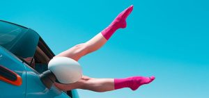Legs with hot pink socks hanging out of a blue car