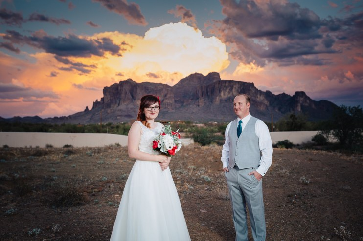 Bride and groom pose in front of the Superstition Mountains