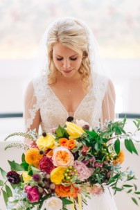 Bride holding a colorful bouquet.