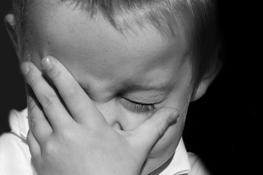 Child crying with hand over eyes