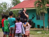 Me at the GK Australia village in Port au Princessa, on the island of Palawan. The camera is a kids' magnet. Got them to say 'G'day Australia' for the camera... it'll definitely make the doco. (IMAGE: CHRIS GRAHAM)