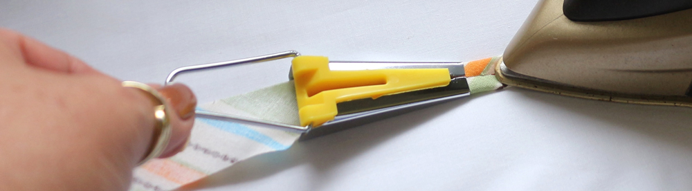 Use the tip of your iron to press the fabric as it comes out of the bias tape maker tool