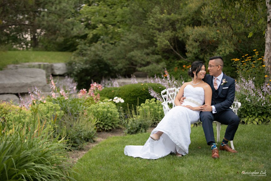 Christopher Luk - Toronto Wedding Photographer - The Manor Event Venue By Peter and Paul's - Main Grand Entrance Trees Walkway Painted White Cast Wrought Iron Bench Seat Bride Groom Golden Hour Creative Portrait Session Natural Candid Photojournalistic Seated Sitting Hug Smile