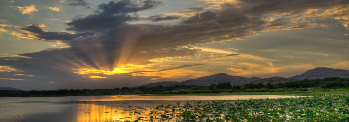 The sun sets over Quanah Parker Lake in the Wichita Mountain Wildlife Refuge while covered in lily pads