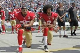 Colin Kaepernick and teammate Eric Reid (left) take a kneel during the national anthem to protest the unarmed killings of Black people by the police.