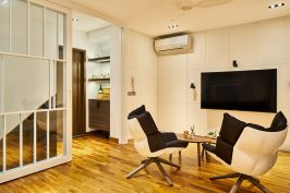 Interior design photography showing living area with tv and bucket seats at simei rise condo in singapore
