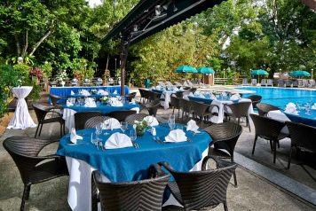Poolside dining at swiss club in singapore with blue tablecloths