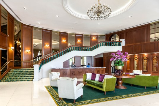 Interior photography of main entrance with staff on telephones behind main desk at the tanglin club in singapore