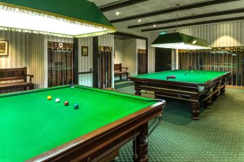 Interior photography of the pool room showing pool tables and pool cues at the tanglin club in singapore