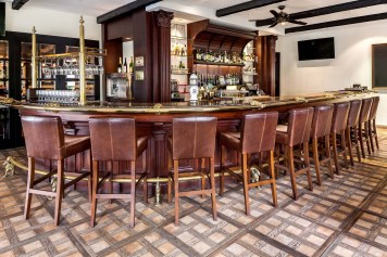 Interior Photography of the wet bar showing bar top and leather chairs at the tanglin club in singapore
