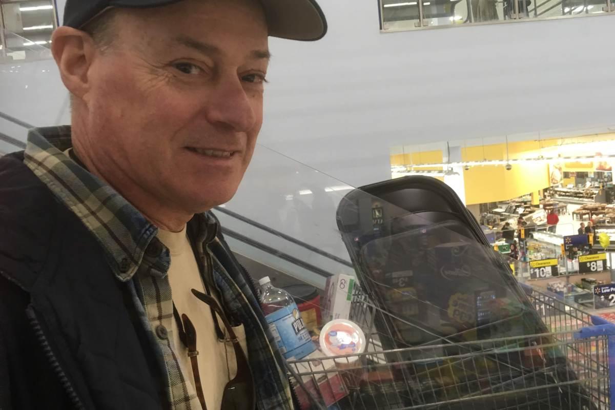Chris riding escalator next to cart.