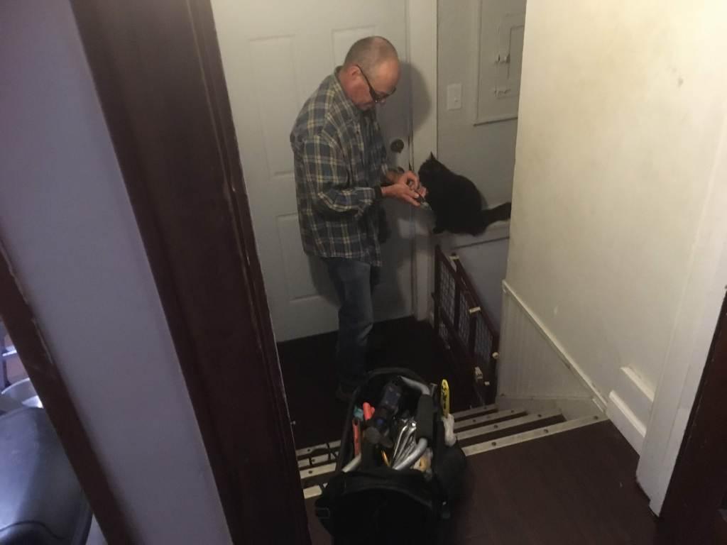 The cat is helping Chris with door repairs. (In reality, she's trying to get him to open the door so she can escape. Haha)The cat is helping Chris with door repairs.