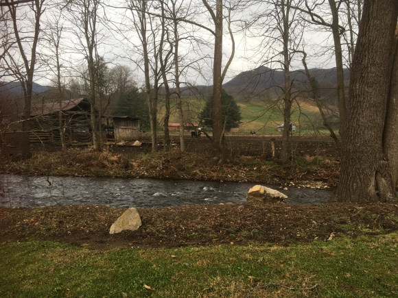 The creek and a barn and some cows with mountains in the distance.