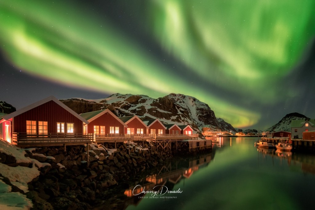 The aurora filling the night sky over some red cabins in Norway.