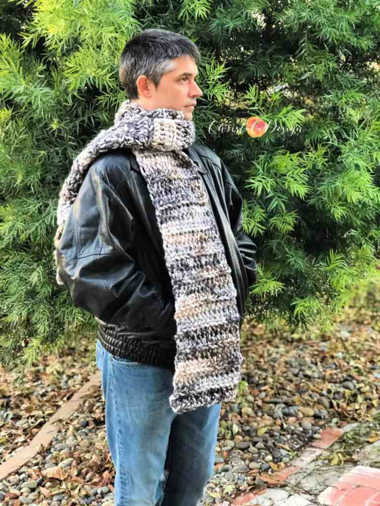 Man in front of tree with cozy super scarf crochet pattern in variegated yarn.