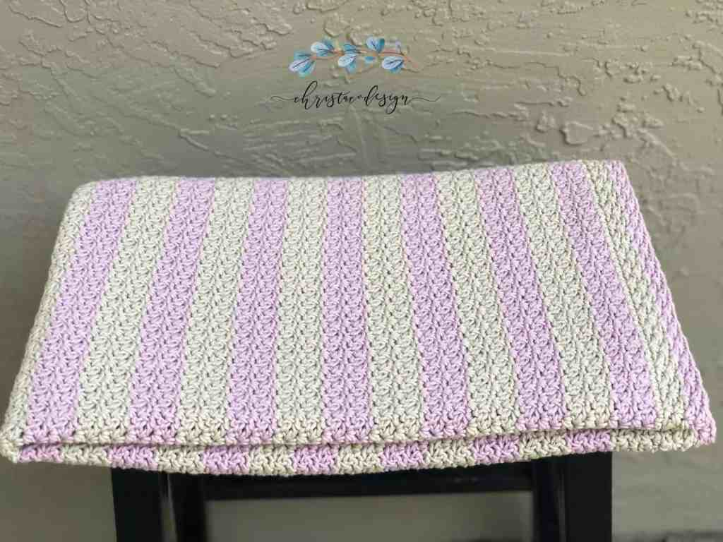 picture of folded pink and grey crochet cotton blanket