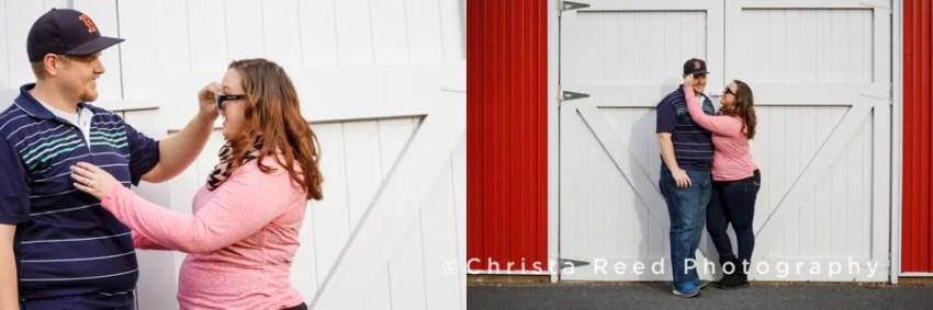 a couple stands next to a red barn for their engagement pictures