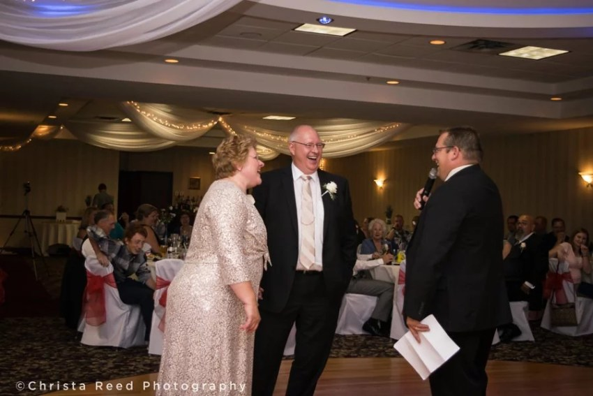 parents of the couple play a game during the wedding reception