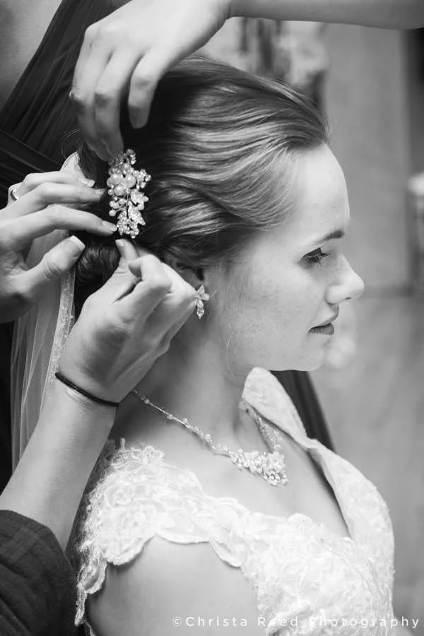 before her wedding in Mankato the bride's friends fasten a hair clip in her hair