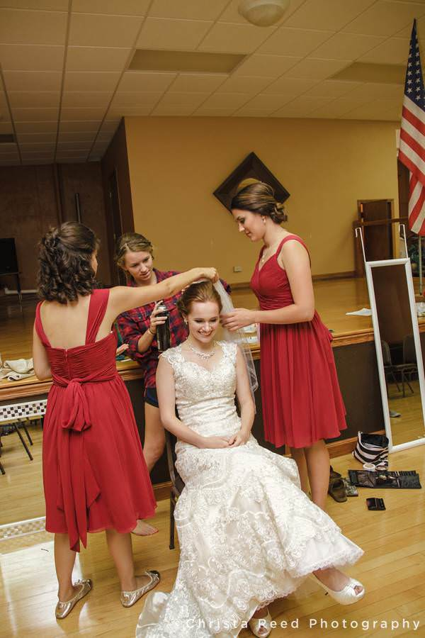 the bride's friends help her with her hair in the mankato church before her wedding