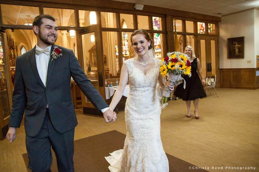 a happy couple leave the sanctuary after their wedding mass at st peter and paul mankato