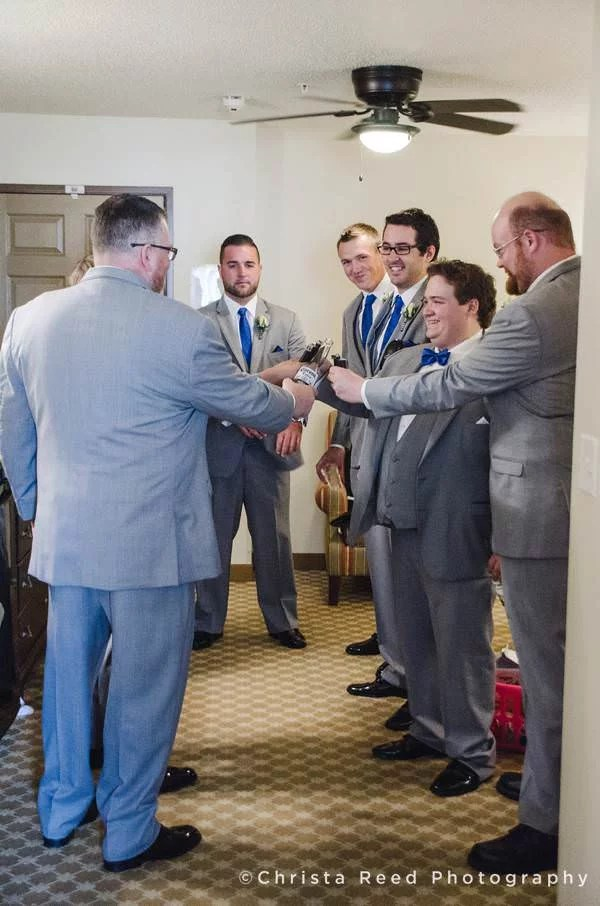 groom and groomsmen have a toast at hotel in chanhassen