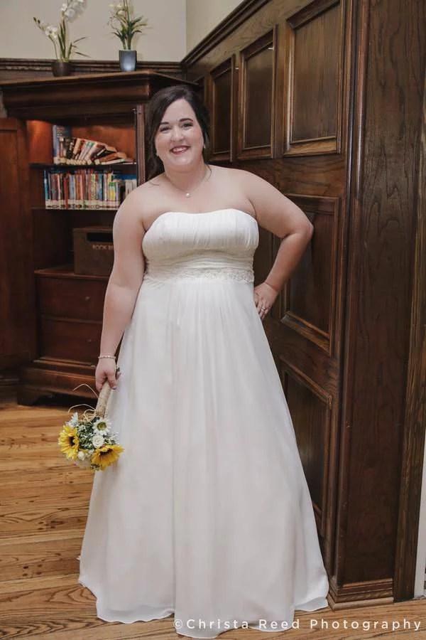 bride poses next to book case