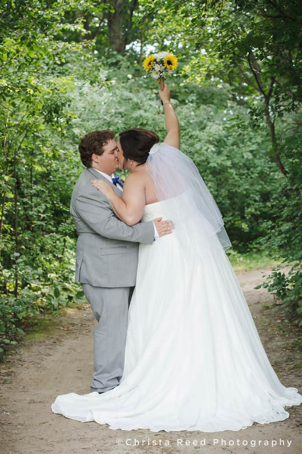 bride and groom kiss in the woods