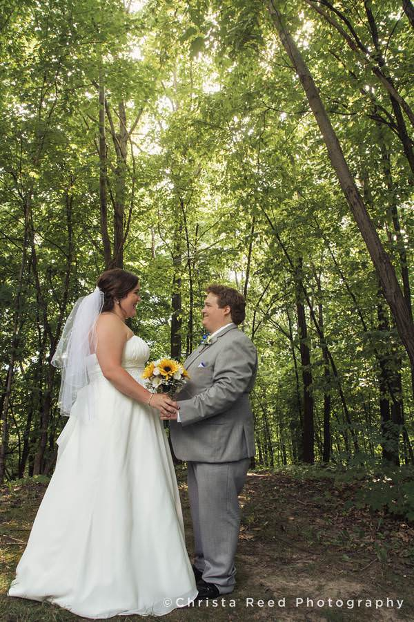 bride and groom hold hands in the woods