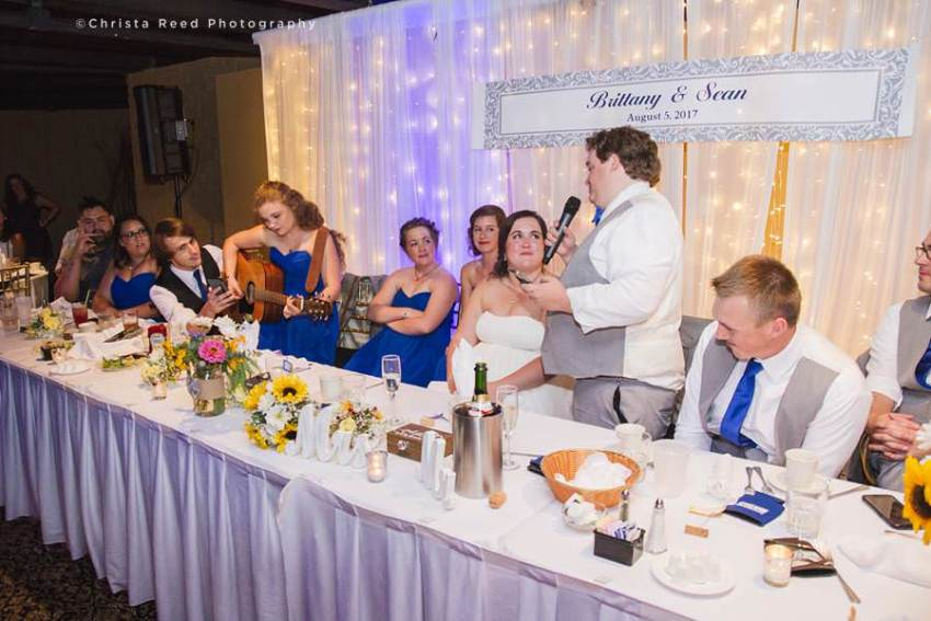 groom sings a song to bride at wedding reception