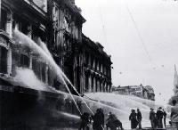 Firemen dampening down the main entrance of Ballantyne's building, Christchurch