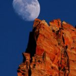 The moon appearing to be suppoted by a natural rock tower